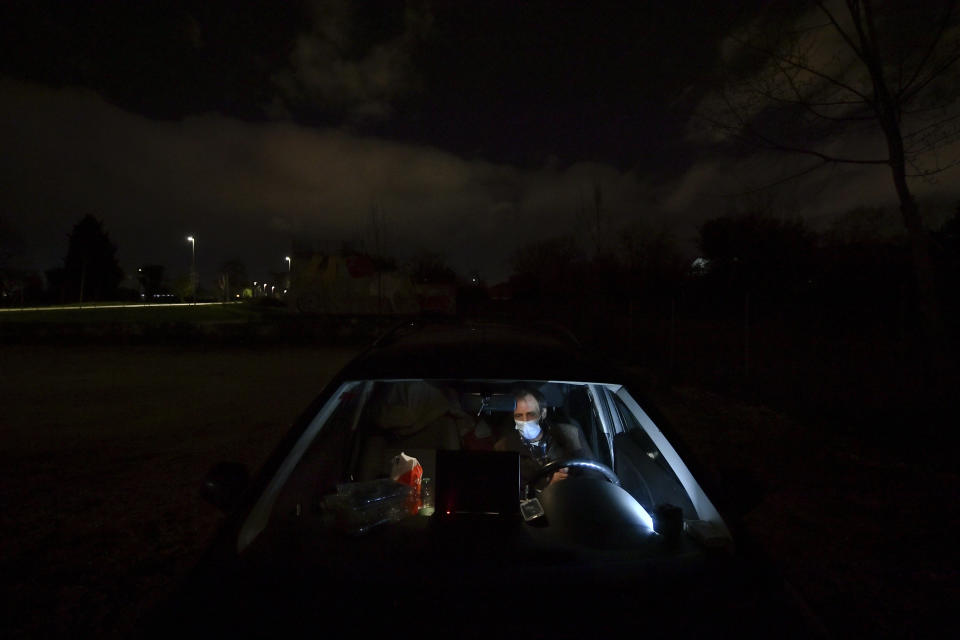 """Juan Jimenez, 60, sits in his car which also serves as his home in Pamplona, northern Spain, Tuesday, March 17, 2021. The 620 euros Jimenez has received in government aid in recent months went to his seven children. """"We are invisible beings,"""" Jimenez said from his car that is cluttered with clothes, blankets, and bags stuffed with all that he owns. (AP Photo/Alvaro Barrientos)"""