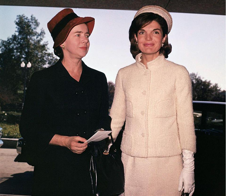 <p>Jackie arrives to a U.S. State Department fashion show dressed in a classic cream tweed skirt suit, pearls, white gloves, and pillbox cap. </p>