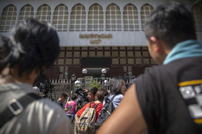 Bystanders look at the Kowloon Mosque a day after it was sprayed with blue-dyed water by a police riot-control vehicle in Hong Kong, Monday, Oct. 21, 2019. Hong Kong officials apologized to leaders of a mosque after riot police sprayed the building's gate and some people nearby with a water cannon as they tried to contain pro-democracy demonstrations. (AP Photo/Mark Schiefelbein)