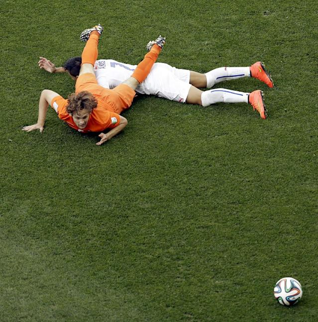 Netherlands' Daley Blind (5) and Chile's Alexis Sanchez (7) fall to the pitch during the group B World Cup soccer match between the Netherlands and Chile at the Itaquerao Stadium in Sao Paulo, Brazil, Monday, June 23, 2014. (AP Photo/Thanassis Stavrakis)