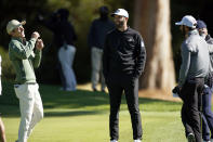 From left, Joaquin Niemann, of Chile, Dustin Johnson and Max Homa talk on the first green after wind suspended play during the third round of the Genesis Invitational golf tournament at Riviera Country Club, Saturday, Feb. 20, 2021, in the Pacific Palisades area of Los Angeles. (AP Photo/Ryan Kang)