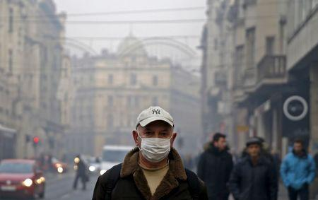 A man wearing a mask walks as smog blankets Sarajevo, Bosnia and Herzegovina December 23, 2015.   REUTERS/Dado Ruvic