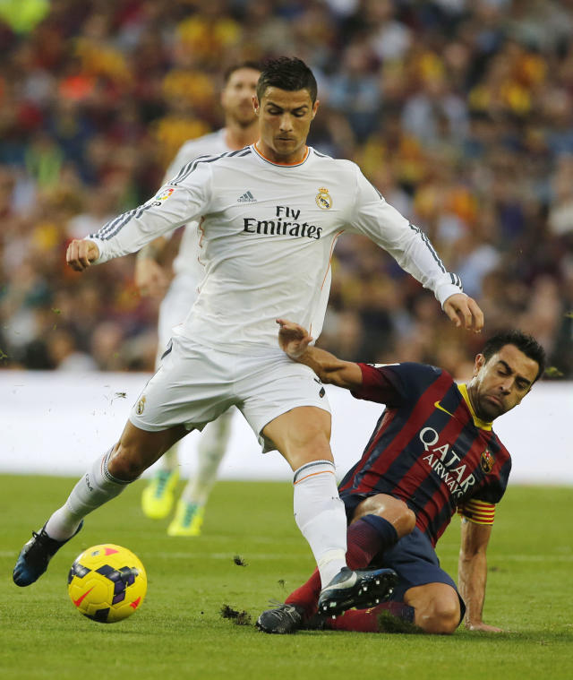 Barcelona's Xavi Hernandez, right, challenges for the ball with Real Madrid's Cristiano Ronaldo during a Spanish La Liga soccer match between Barcelona F.C. and Real Madrid at the Camp Nou stadium in Barcelona, Spain, Saturday, Oct. 26, 2013. (AP Photo/Emilio Morenatti)