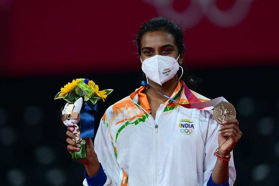 India's P. V. Sindhu poses with her women's singles badminton bronze medal at a ceremony during the Tokyo 2020 Olympic Games at the Musashino Forest Sports Plaza in Tokyo on August 1, 2021. (Photo by Pedro PARDO / AFP) (Photo by PEDRO PARDO/AFP via Getty Images)