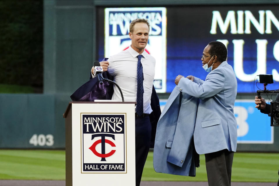 Former Minnesota Twins player Justin Morneau, left, sheds his jacket as former Twins great and Hall of Famer Rod Carew presents the new jacket after Morneau was inducted into the Twins' Hall of Fame prior to a baseball game against the Toronto Blue Jays, Saturday, Sept. 25, 2021, in Minneapolis. (AP Photo/Jim Mone)
