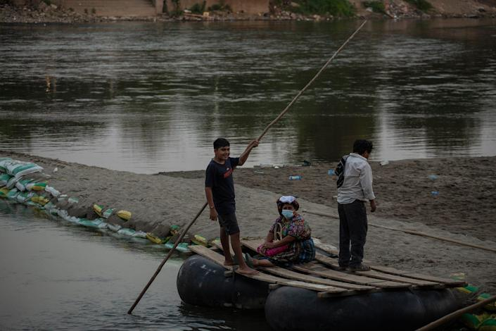 A kid working as a rafter crosses a Guatemalan woman from the Mexican side of the Suchiate River.