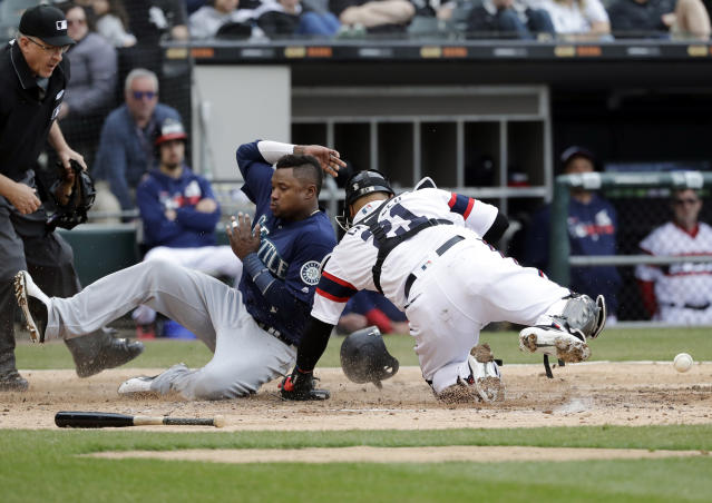 Seattle Mariners' Tim Beckham, left, scores on a three-run double by Daniel Vogelbach as Chicago White Sox catcher Welington Castillo missed the ball during the third inning of a baseball game in Chicago, Sunday, April 7, 2019. (AP Photo/Nam Y. Huh)