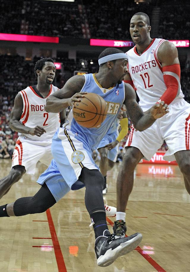 Denver Nuggets' Ty Lawson, center, drives the ball between Houston Rockets Patrick Beverley (2) and Dwight Howard (12) in the first half of an NBA basketball game Saturday, Nov. 16, 2013, in Houston. (AP Photo/Pat Sullivan)