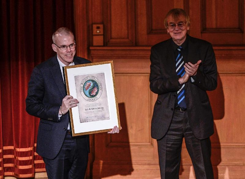 Bill McKibben (L) representing the grassroots organisation 350.org (USA) receives the Right Livelihood Award from Jakob von Uexkull (R) during a ceremony at the Swedish Parliament in Stockholm on December 1, 2014 (AFP Photo/Pontus Lundahl)