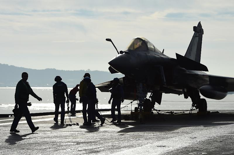 French naval tecnicians work on the flight deck of the aircraft carrier Charles-de-Gaulle at a military port in the southern French city of Toulon, on November 18, 2015
