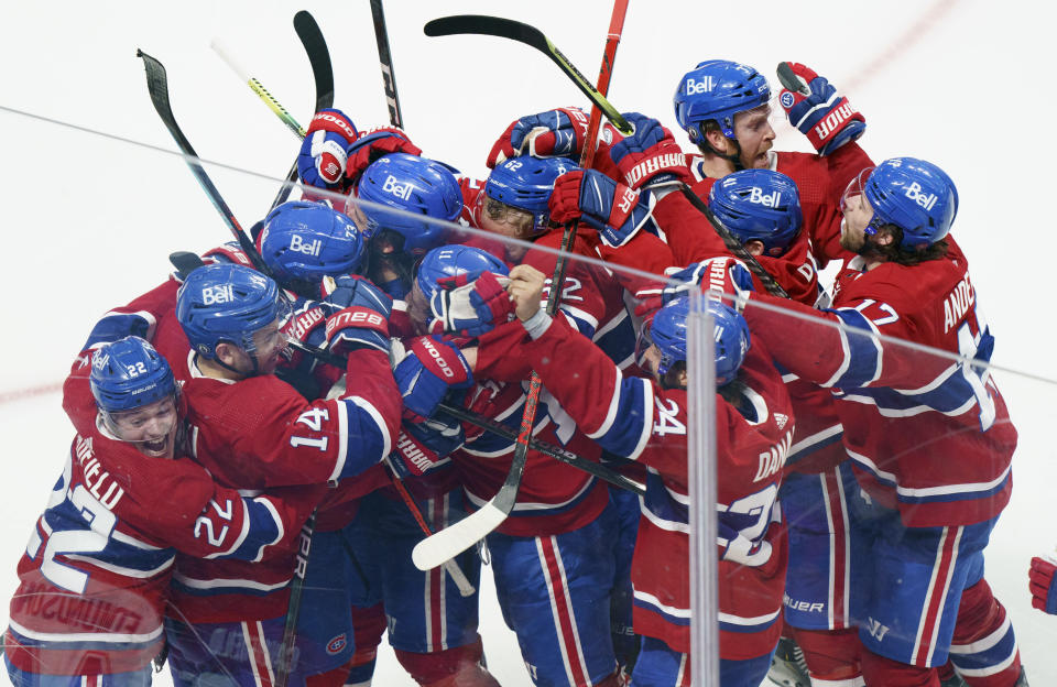 Montreal Canadiens right wing Tyler Toffoli (73) is mobbed by teammates after scoring the winning goal following overtime NHL Stanley Cup playoff hockey action against the Winnipeg Jets in Montreal, Monday, June 7, 2021. (Paul Chiasson/The Canadian Press via AP)