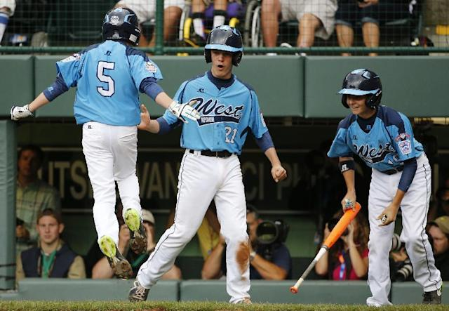 Las Vegas' Justin Hausner (5) leaps on home plate and celebrates with teammates Austin Kryszczuk (21) and Brad Stone, right, after all three runs scored on a double by Drew Laspaluto off Chicago's Joshua Houston in the first inning of a United States Championship game at the Little League World Series in South Williamsport, Pa., Saturday, Aug. 23, 2014. (AP Photo/Gene J. Puskar