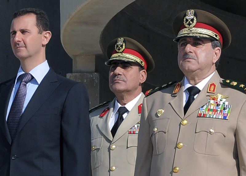 FILE - In this Thursday Oct. 6, 2011 photo released by the Syrian official news agency SANA, Syrian President Bashar Assad, left, stands next to Syrian Defense Minister Gen. Dawoud Rajha, right, during a ceremony to mark the 38th anniversary of the October 1973 Arab-Israeli war, in Damascus, Syria. Syria's state-run TV says the country's defense minister has been killed in a suicide blast in the capital. Wednesday's attack struck the National Security building in Damascus during a meeting of Cabinet ministers and senior security officials. (AP Photo/SANA, File)