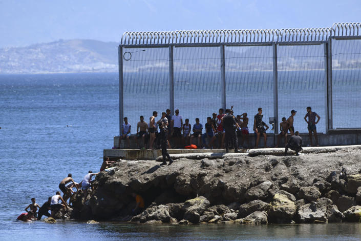 Spanish Guardia Civil officers try to stop people from Morocco entering into the Spanish territory at the border of Morocco and Spain, at the Spanish enclave of Ceuta on Monday, May 17, 2021. Authorities in Spain say that around 1,000 Moroccan migrants have crossed into Spanish territory (Antonio Sempere/Europa Press via AP)
