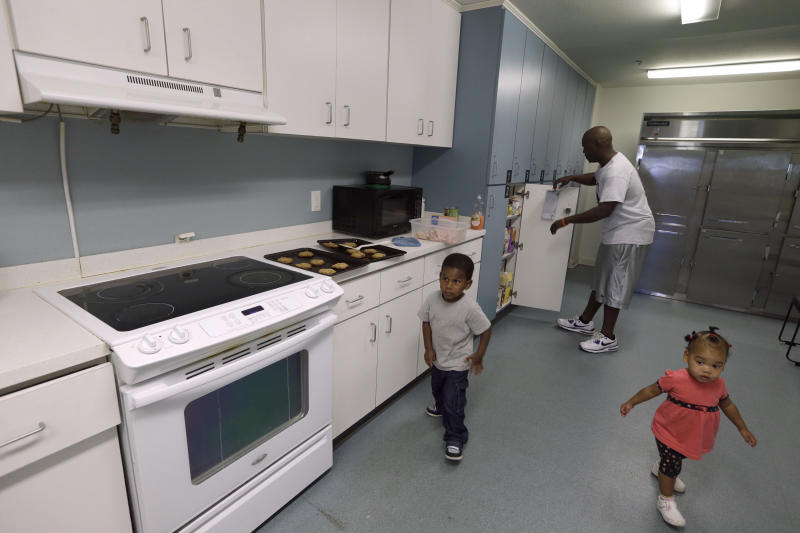In this photo taken Thursday, Oct. 10, 2013, Donovan James, top, prepares food for his family in a communal kitchen as two of his children Naomi, 1, right, and Jeremiah, 3, walk through the area at Our House, a nonprofit organization that provides childcare, shelter and other programs for working homeless people in Little Rock, Ark. Private donors are helping fill in the gaps left by missing funds due to the partial government shutdown. (AP Photo/Danny Johnston)