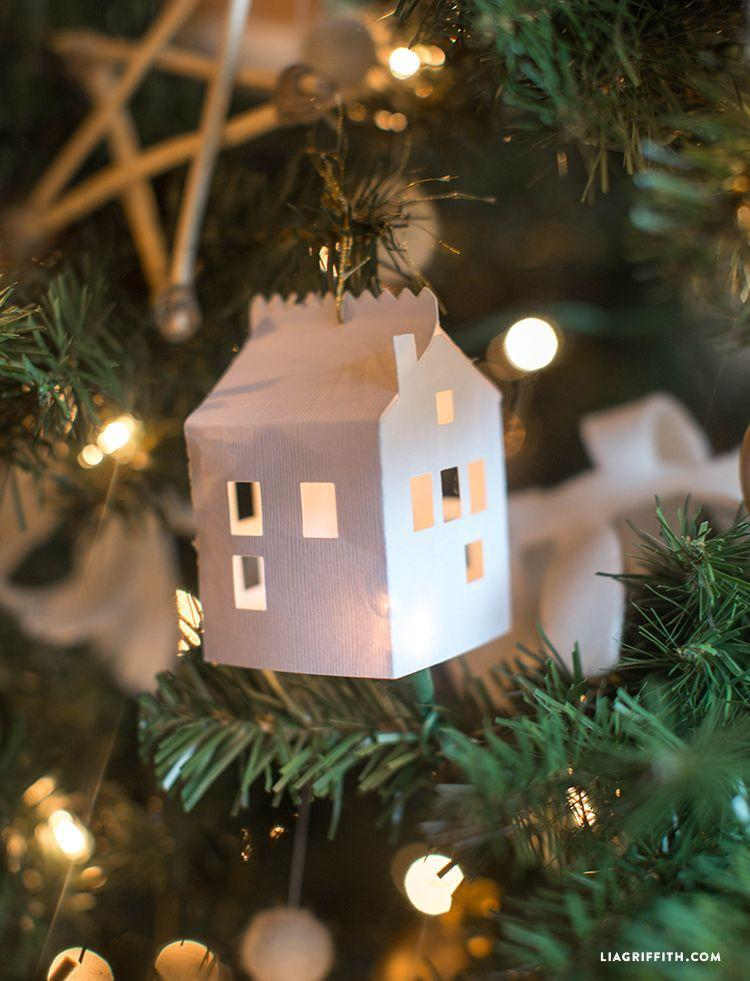 """<p>These tiny paper houses are too cute. Hung from a well-lit tree, they'll quickly add coziness and warmth to any living room.</p><p><strong>Get the tutorial at <a href=""""https://liagriffith.com/diy-paper-house-christmas-ornament/"""" rel=""""nofollow noopener"""" target=""""_blank"""" data-ylk=""""slk:Lia Griffith"""" class=""""link rapid-noclick-resp"""">Lia Griffith</a>.</strong></p><p><strong><a class=""""link rapid-noclick-resp"""" href=""""https://www.amazon.com/Cardstock-American-Crafts-textured-cardstock/dp/B001O5UJGK?tag=syn-yahoo-20&ascsubtag=%5Bartid%7C10050.g.1070%5Bsrc%7Cyahoo-us"""" rel=""""nofollow noopener"""" target=""""_blank"""" data-ylk=""""slk:SHOP CARDSTOCK"""">SHOP CARDSTOCK</a></strong></p>"""