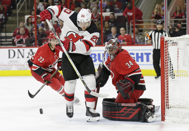 Carolina Hurricanes goalie Petr Mrazek (34), of the Czech Republic, watches New Jersey Devils' Blake Coleman (20) in front of the net during the first period of an NHL hockey game in Raleigh, N.C., Thursday, April 4, 2019. (AP Photo/Gerry Broome)