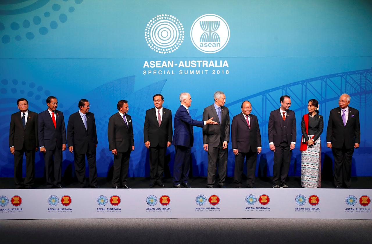 Australia's Prime Minister Malcolm Turnbull gestures to ASEAN leaders Laos' Prime Minister Thongloun Sisoulith, Indonesia's President Joko Widodo, Cambodia's Prime Minister Hun Sen, Brunei's Sultan and Prime Minister Sultan Bokliah, Thailand's Prime Minister Prayut Chan-O-Cha, Singapore's Prime Minister Lee Hsien Loong, Vietnam's Prime Minister Nguyen Xuan Phuc, Philippines' Secretary of Foreign Affairs Alan Peter Cayetano, Myanmar's State Counsellor Aung San Suu Kyi and Malaysia's Prime Minister Najib Razak to leave the stage after posing for the Leaders Welcome and Family Photo at the one-off summit of 10-member Association of Southeast Asian Nations (ASEAN) in Sydney, Australia, March 17, 2018.     REUTERS/David Gray