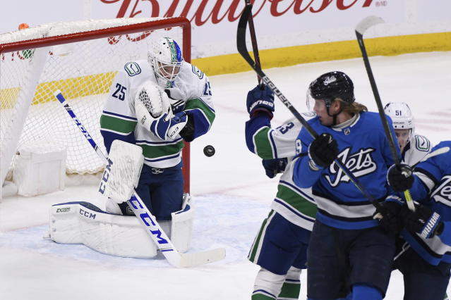 Vancouver Canucks goaltender Jacob Markstrom (25) makes a save against the Winnipeg Jets during the first period of an NHL hockey game Tuesday, Jan. 14, 2020, in Winnipeg, Manitoba. (Fred Greenslade/The Canadian Press via AP)