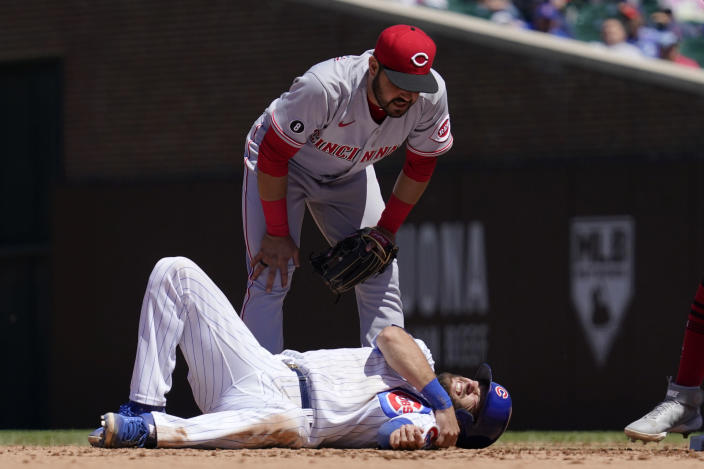 Cincinnati Reds shortstop Eugenio Suarez, top, looks down at Chicago Cubs' David Bote after an injury during the fourth inning of a baseball game in Chicago, Saturday, May 29, 2021. (AP Photo/Nam Y. Huh)