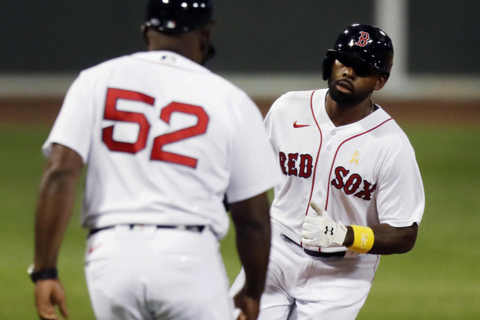 Boston Red Sox's Jackie Bradley Jr. celebrates his two-run home run with third base coach Carlos Febles (52) during the second inning of the team's baseball game against the Toronto Blue Jays, Saturday, Sept. 5, 2020, in Boston. (AP Photo/Michael Dwyer)