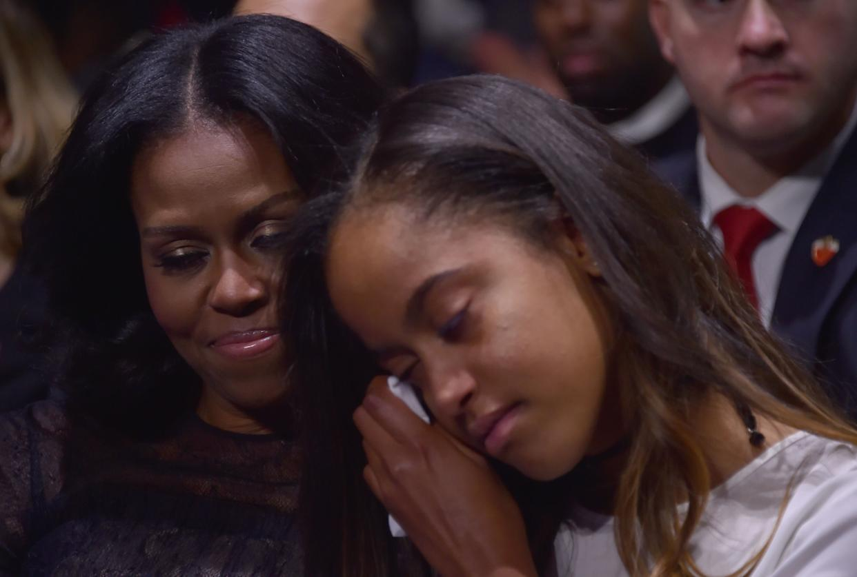 Michelle Obama holds her daughter Malia during President Obama's farewell address.