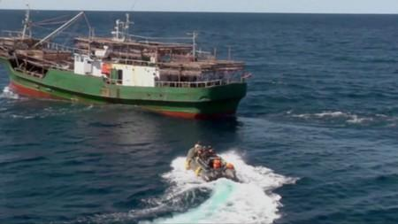 A still image shows a boat with Russian border guards sailing towards a North Korean vessel to detain it and crew members for poaching in waters that Moscow considers its exclusive economic zone
