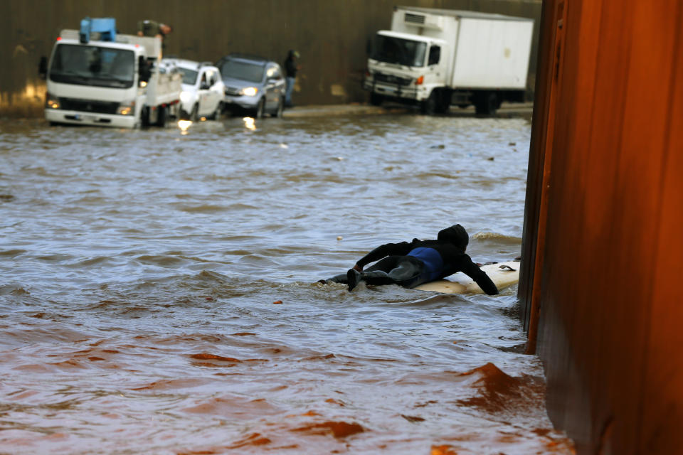 A man uses a surfboard to pass through a flooded tunnel in Beirut's southern suburb of Ouzai, Lebanon, Monday, Dec. 9, 2019. A rainstorm has paralyzed parts of Lebanon's capital Beirut, turning streets to small rivers, stranding motorists inside their vehicles and damaging homes in some areas (AP Photo/Bilal Hussein)