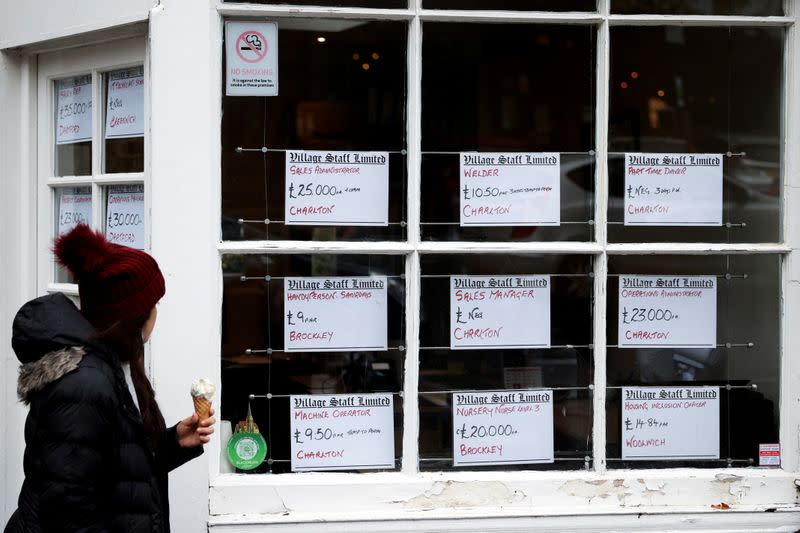 FILE PHOTO: A person looks at advertisements in the window of a job agency in London