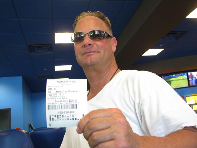 Michael Black, of Tinton Falls, N.J., holds a betting slip he got at Monmouth Park racetrack in Oceanport after making a bet on a baseball game between the Chicago Cubs and Los Angeles Dodgers, Tuesday, June 19, 2018. Monmouth Park and Atlantic City's Borgata casino say they're pleased with the extra revenue sports betting has brought in during the first few days it has been legal in New Jersey. (AP Photo/Wayne Parry)