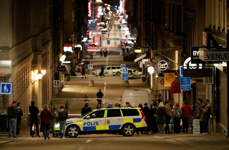 People stand behind a cordon as police work at the scene of a truck attack that killed four people outside a busy department store in central Stockholm on April 7, 2017