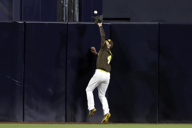 San Diego Padres center fielder Wil Myers makes the catch at the wall for the out on Cincinnati Reds' Yasiel Puig during the seventh inning of a baseball game Friday, April 19, 2019, in San Diego. (AP Photo/Gregory Bull)