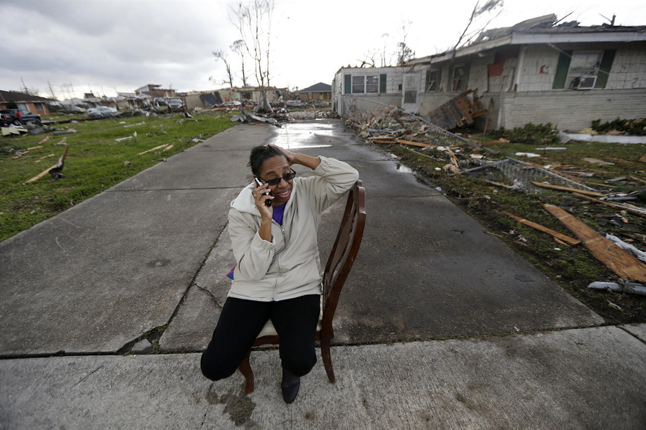<p>Claire White sits in a chair and talks on her phone across the street from her home, which was destroyed by a tornado that tore through a New Orleans neighborhood, Feb. 7, 2017. (Photo: Gerald Herbert/AP) </p>