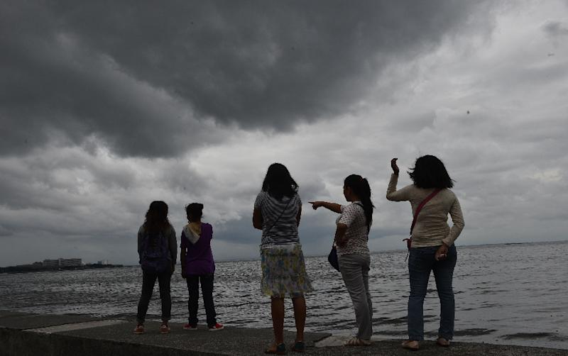 People watch as storm clouds gather around Manila Bay on October 16, 2016, after Typhoon Sarika passed north of the capital overnight (AFP Photo/Ted Aljibe)