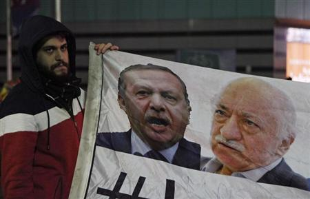 A demonstrator hold pictures of Turkey's PM Erdogan and Turkish cleric Gulen, during a protest in Istanbul