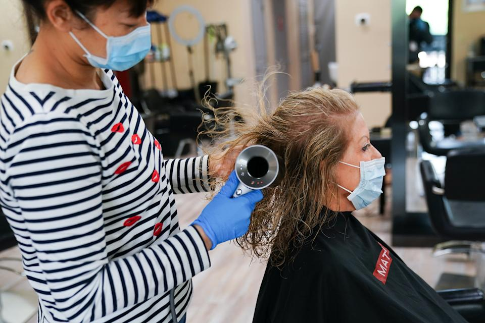 A stylist wearing a protective mask dries a customer's hair at a hair salon in Atlanta, Georgia, U.S., on Friday, March 24, 2020. Georgia's hair salons, tattoo parlors, bowling alleys, and other nonessential businesses were permitted to reopenon Friday,after Governor Brian Kemp announced earlier this week that he'd ease the state's stay-at-home order. Photographer: Elijah Nouvelage/Bloomberg