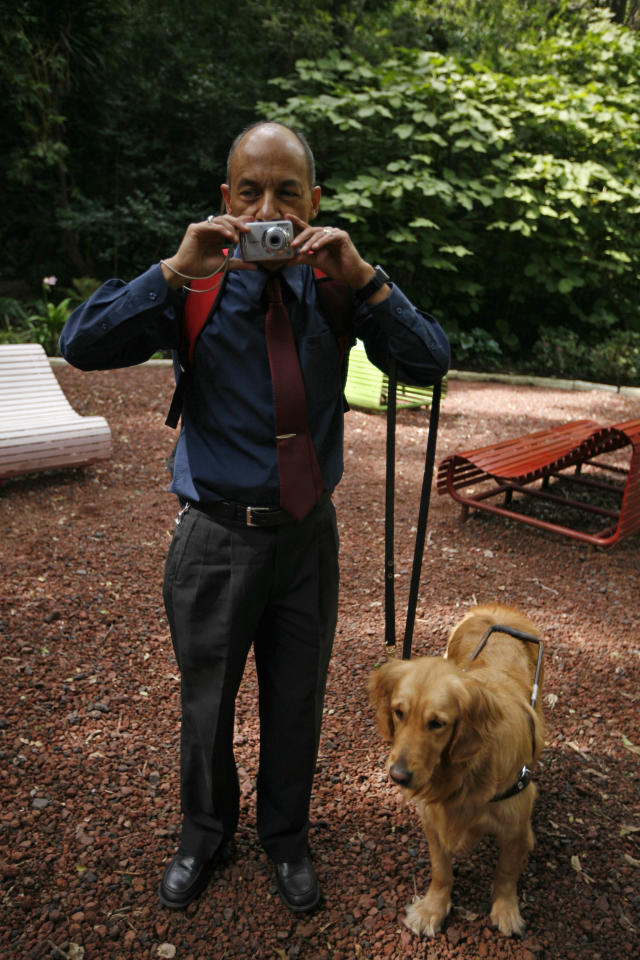 In this photo taken Sept. 7, 2011, Jose Antonio Dominguez places the camera under his nose as he prepares to take a photograph at a park in Mexico City Sept. 7, 2011. Dominguez is one of 30 visually impaired or blind people learning photography with the help of the Mexico City foundation Ojos Que Sienten, or Eyes That Feel. (AP Photo/Marco Ugarte)