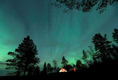 FILE PHOTO: The Aurora Borealis (Northern Lights) is seen over a mountain camp north of the Arctic Circle, near the village of Mestervik, Norway September 30, 2014.REUTERS/Yannis Behrakis/File Photo