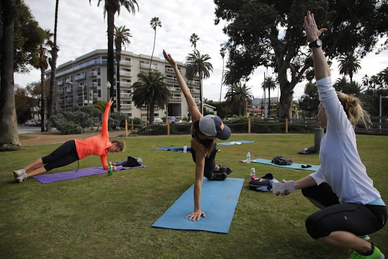 In this photo taken Tuesday, Dec. 18, 2012, Ellye O'Brian, left, Jennifer Levi, center, work out with fitness instructor Dana McCaw during their fitness class at Palisades Park in Santa Monica, Calif. City officials say the park is being overrun by people operating everything from boot camps to yoga classes to massage therapy sessions. Officials are considering making such operators cut the city in on 15 percent of their profits and pay an annual $100 permit fee for the right to do business in the park. (AP Photo/Jae C. Hong)