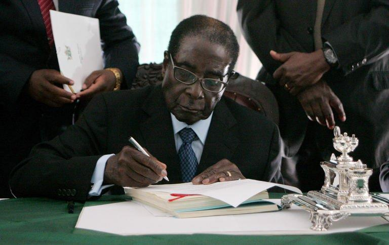 Zimbabwe President Robert Mugabe signs into law Zimbabwe's new constitution at the State House in Harare on May 22 2013