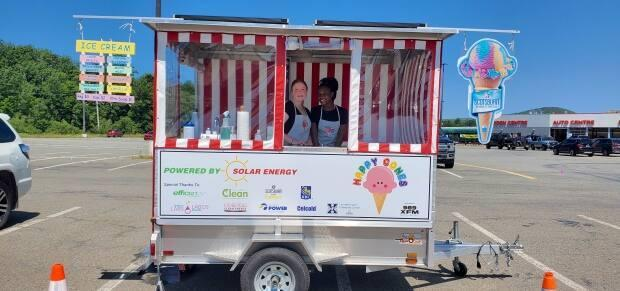 Nicky Nicholson, left, is seen with a co-worker inside the Happy Cones ice cream trailer. Nicholson opened the entirely solar-powered trailer in July. (Peter Nicholson - image credit)