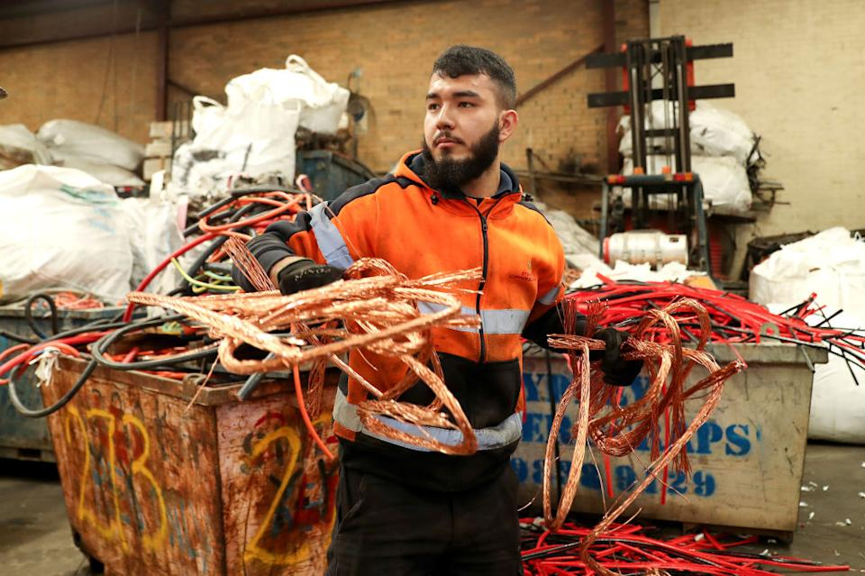 A worker prepares pure copper cables for export to China at a Sydney Copper Scraps facility in Sydney.