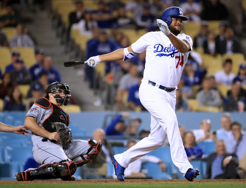 LOS ANGELES, CA - MAY 18: Kenley Jansen #74 of the Los Angeles Dodgers hits an infield single in front of J.T. Realmuto #11 of the Miami Marlins during the eighth inning at Dodger Stadium on May 18, 2017 in Los Angeles, California. (Photo by Harry How/Getty Images)