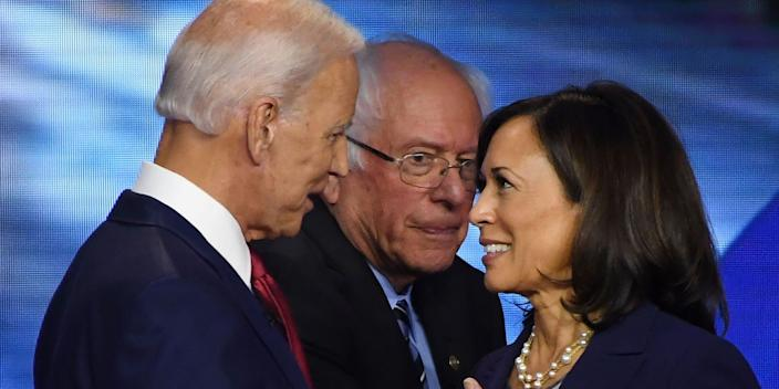 Democratic presidential hopefuls Former Vice President Joe Biden (L) and California Senator Kamala Harris (R) speak while Vermont Senator Bernie Sanders walks by after the third Democratic primary debate.