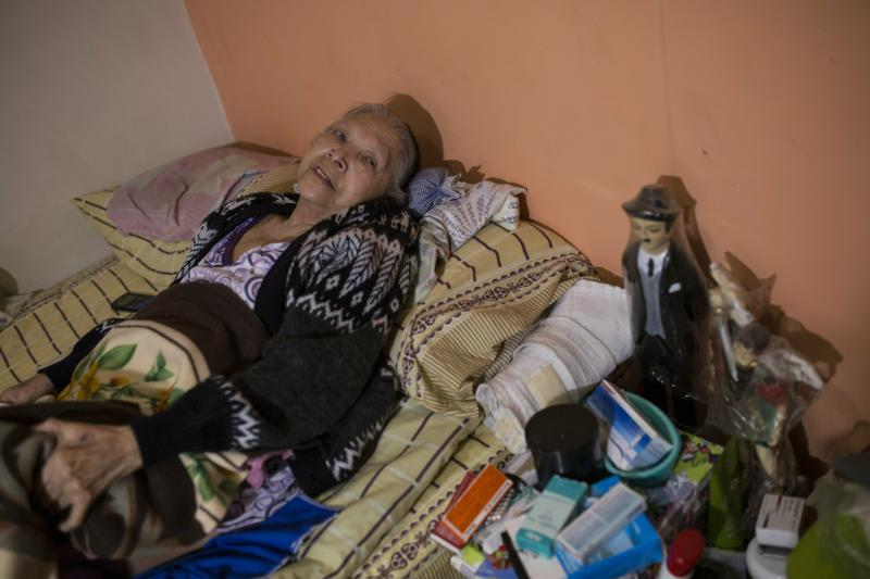 "In this Feb. 4, 2019 photo, diabetes patient Aminta Villamizar lies on her bed next to a statue of Dr. Jose Greogrio Hernandez, a 19th century Venezuelan doctor who treated the poor and is revered throughout the country as a saint, in Caracas, Venezuela. ""I was a person who worked my entire life, but this sickness destroyed me,"" she said, complaining of joint pain and blurry vision. ""If we don't receive help, we'll have to resign ourselves to God's will."" (AP Photo/Rodrigo Abd)"