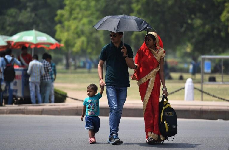 <p>An Indian family visits the India Gate monument on a hot day in New Delhi on April 14, 2017. / AFP PHOTO / Prakash SINGH </p>