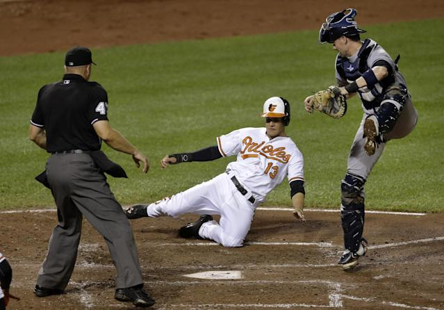 Baltimore Orioles' Manny Machado, center, slides between New York Yankees catcher Chris Stewart, right, and home plate umpire Jeff Nelson for a run on a double by Chris Davis in the third inning of a baseball game, Wednesday, Sept. 11, 2013, in Baltimore. (AP Photo/Patrick Semansky)
