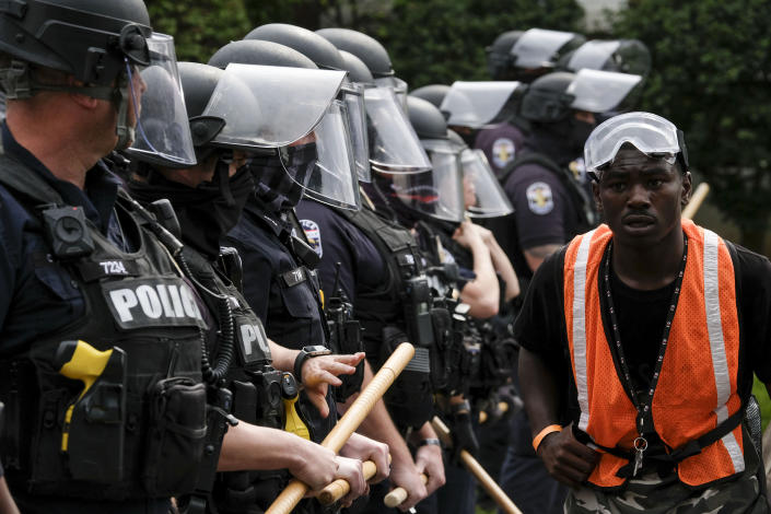 A protestor marches by a police line in downtown Louisville, Kentucky, on September 23, 2020. (Photo by JEFF DEAN/AFP via Getty Images)