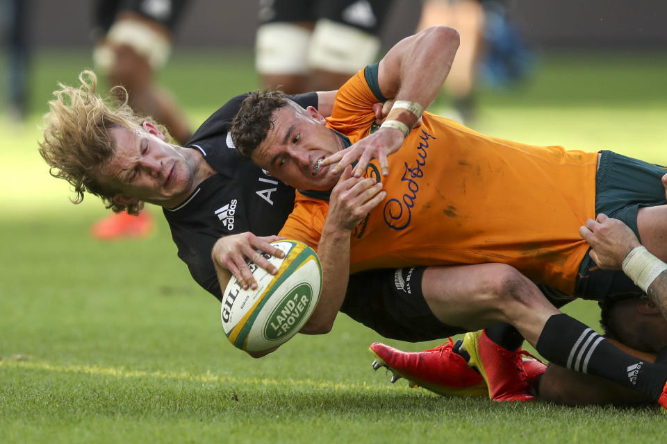 Australia's Tom Banks scores a try in the tackle of New Zealand's Damian McKenzie during the Rugby Championship game between the All Blacks and the Wallabies in Perth, Australia, Sunday, Sept. 5, 2021. (AP Photo/Gary Day)