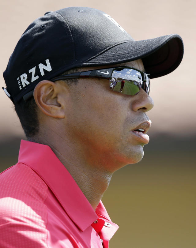 Golfer Tiger Woods watches as Luke Guthrie takes a hit on the first hole during the final round of the Honda Classic golf tournament on Sunday, March 2, 2014, in Palm Beach Gardens, Fla. (AP Photo/Wilfredo Lee)